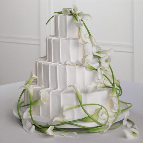Γαμήλια τούρτα διακοσμημένη με φρέσκα λουλούδια.